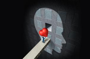Hombre encajando un corazón en un perfil de una cabeza