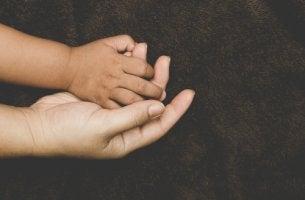 Mano de niño agarrando la de su madre para representar el apego en los niños adoptados