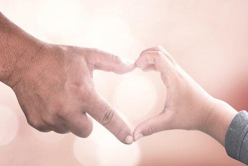 Manos de un niño y de su padre formando un corazón
