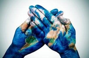Manos pintadas con la bola del mundo como ejemplo de la psicología cultural