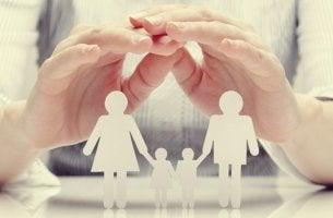 Manos sobre una familia de papel para representar la adopción