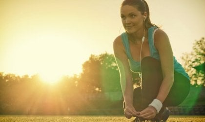 mujer arrodillada con auriculares haciendo ejercicio físico