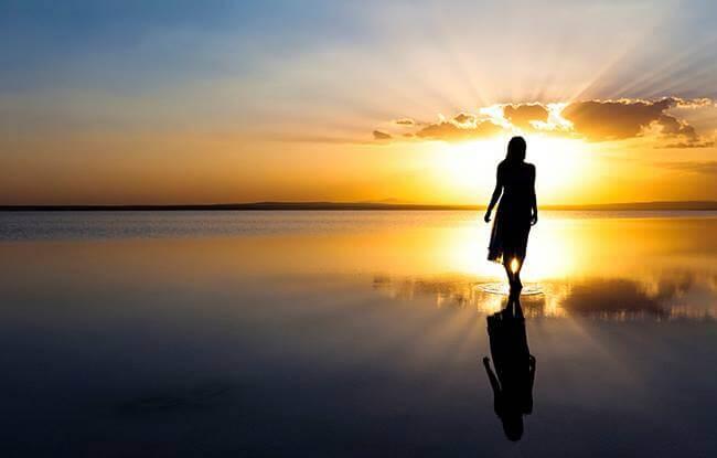 mujer avanzando por playa representando las frases para recuperar la energía positiva