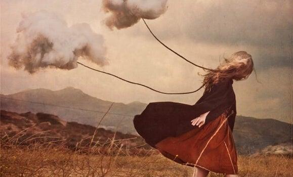 Mujer avanzando con dos nubes sufriendo la ausencia de un ser querido