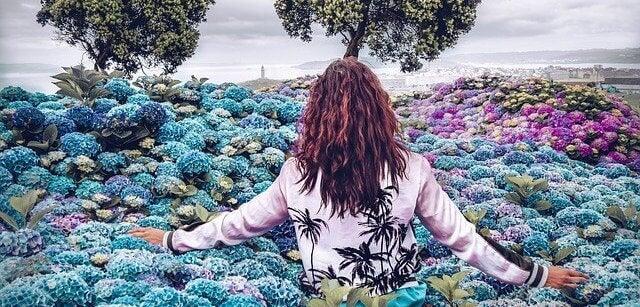 Mujer avanzando entre flores