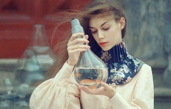chica mirando bombilla donde hay un pez pensando en las leyes de las emociones