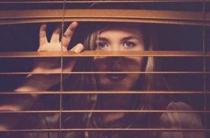 Mujer con indefensión aprendida mirando detrás de una ventana