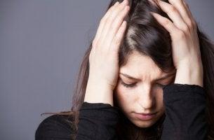 Mujer con trastorno mixto ansioso-depresivo con manos en la cabeza