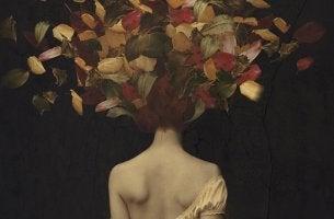 mujer de espaldas con hojas en el cabello librándose de la tristeza