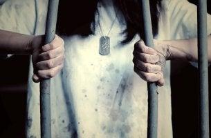 Mujer intentando salir de una jaula