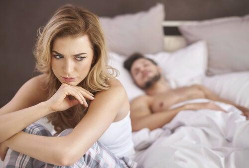 Mujer preocupada en la cama como representación de la anorgasmia femenina