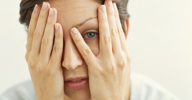 A woman covering her face and one eye.