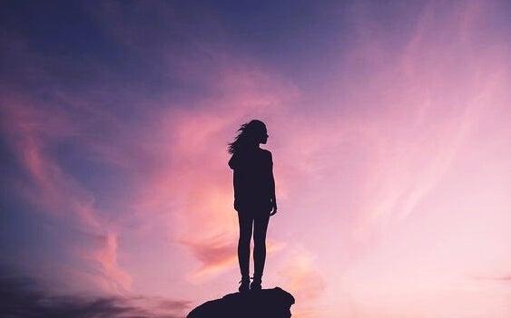 mujer sobre una roca demostrando que la actitud es la fuerza más poderosa