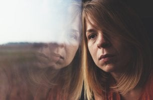 Mujer triste apoyada en una ventana