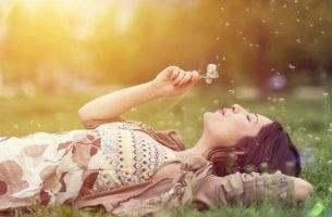 Mujer tumbada en el campo soñando