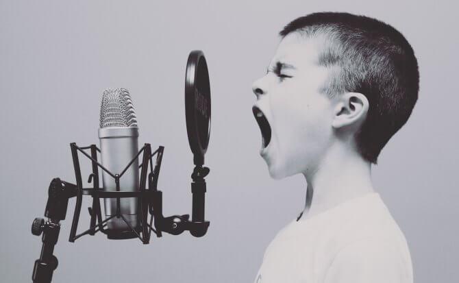 niño elevando tono de voz mientras habla ante microfono
