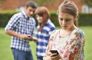 Niña mirando el móvil mientras recibe amenazas