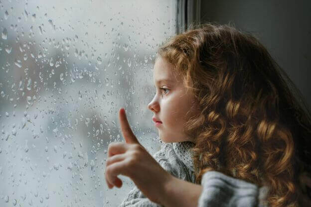 girl looking out rainy window
