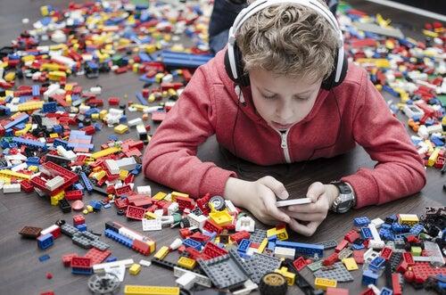 Niño con móvil rodeado de juguetes