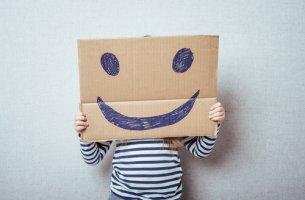 Niño con un cartón que tiene una cara sonriente dibujada