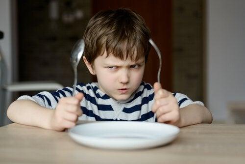 Niño con síndrome del emperador enfadado porque no quiere comer