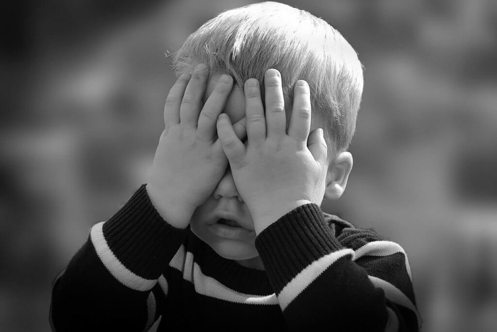 Niño con las manos sobre los ojos para representar el estrés infantil