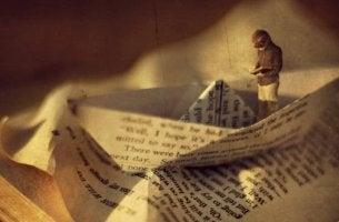 Niño leyendo un libro sobre un barco de papel