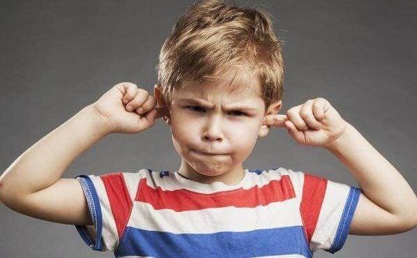 Niño tapándose los oídos