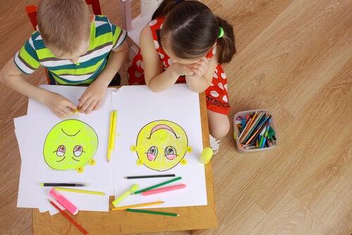 Niños dibujando caras de emociones por la alfabetización emocional