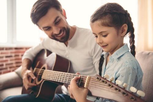 Padre enseñando a su hija a tocar la guitarra