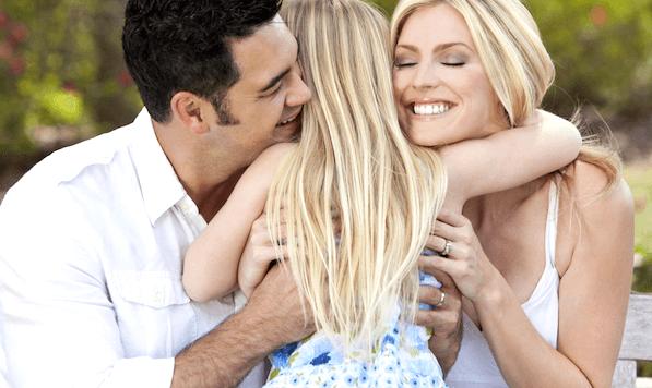 papás abrazando a su hija representado a los padres de los pequeños narcisistas