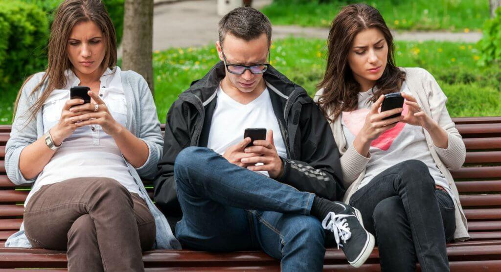 amigos mirando móvil y sufriendo el síndrome de Tinderella