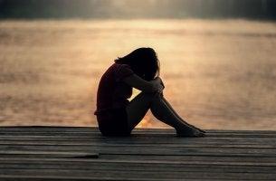 Chica adolescente llorando en el puerto por la violencia en las parejas de adolescentes como la suya