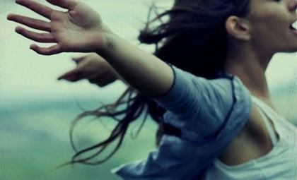 chica con los brazos abiertos representando a las personas autorrealizadas