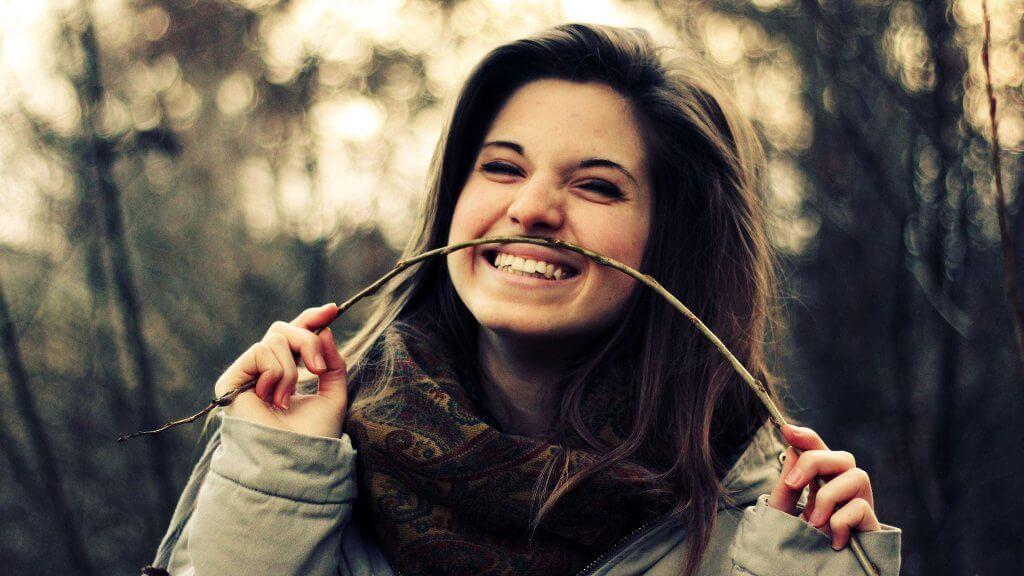 Chica sonriendo con rama de árbol