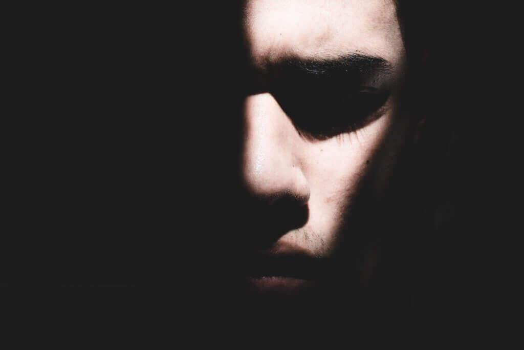 Hombre a oscuras con luz sobre su cara
