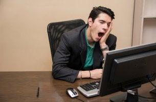 Hombre bostezando en el trabajo por el síndrome de Boreout
