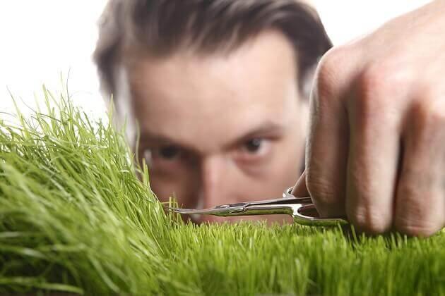 Hombre con trastorno de personalidad obsesiva cortando el cesped