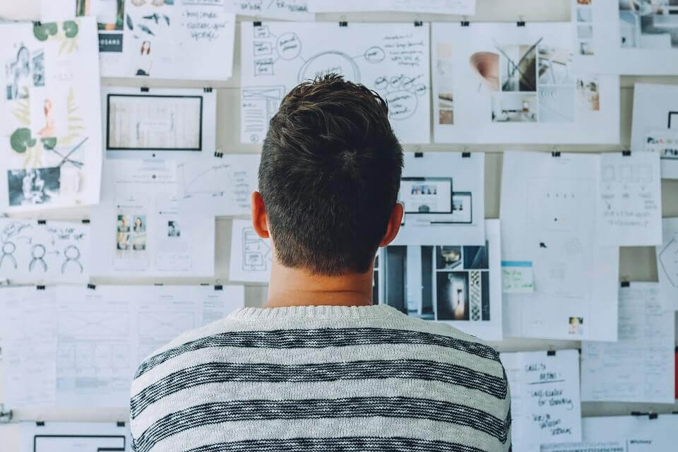 Hombre mirando papeles en la pared