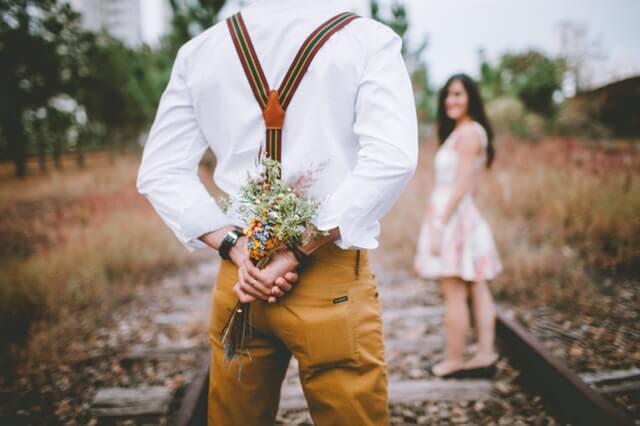 Hombre regalando flores haciendo benching