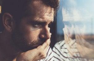 Hombre triste ante un cristal
