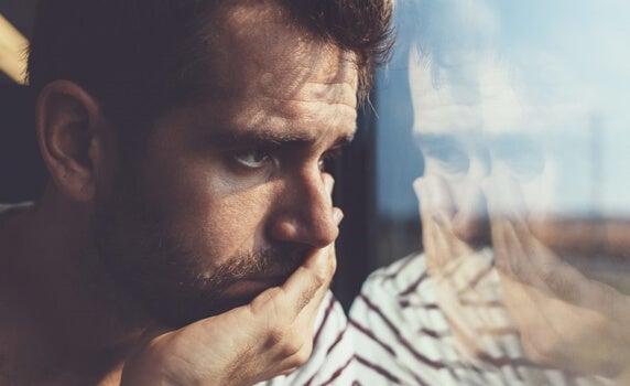 hombre triste ante un cristal representando las frases de Anna Freud