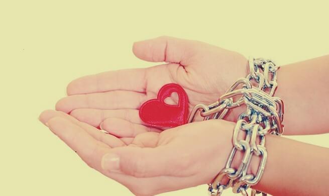 Manos encadenadas con corazón simbolizando el apego