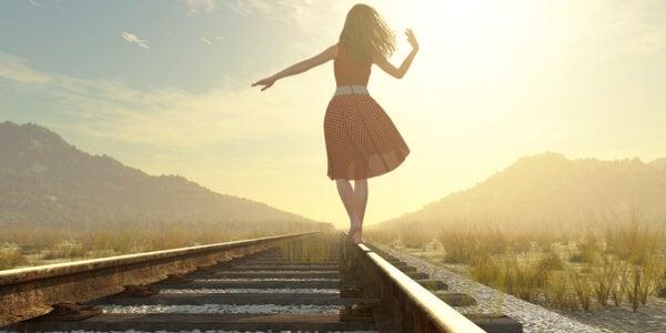Mujer caminando por la vía del tren