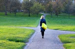 Mujer en mitad de cuatro caminos para representar la decisión a través de sesgos cognitivos
