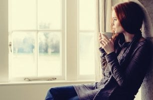 mujer frente a ventana que disfruta de sus pausas