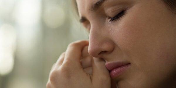 Mujer llorando y secándose sus lágrimas