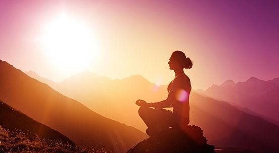 Mujer meditando en una montaña al amanecer