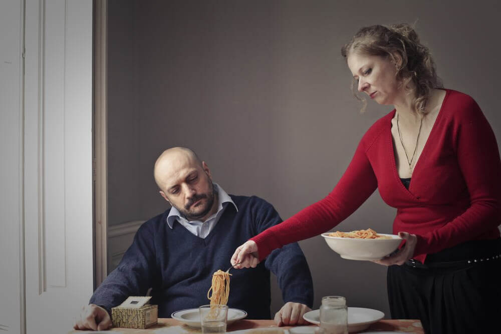 Mujer sirviendo la comida a su marido