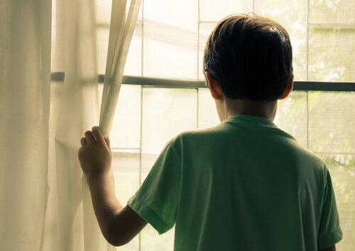 Niño con discapacidad intelectual mirando por la ventana